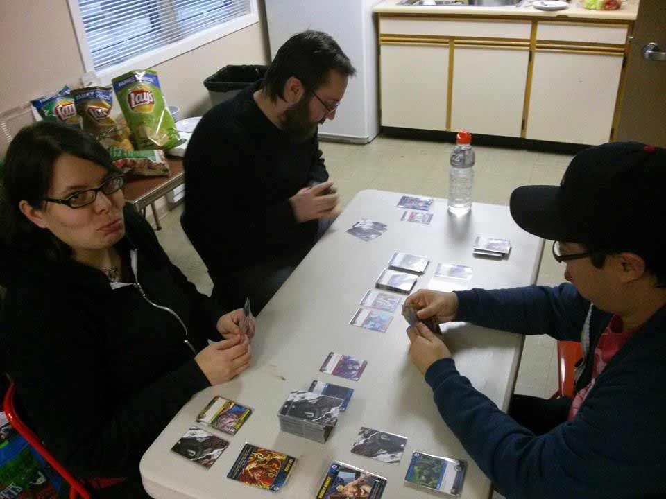 dudes and dudette playing DC Deckbuilding game